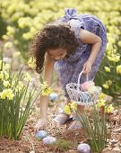 Girl picking up Easter eggs
