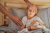 Sick Boy With Thermometer Laying In Bed And Father Hand Taking Temperature. Father Checking Temperat poster