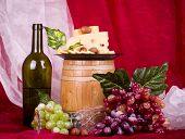 Beautiful composition with wine, grape, cheese and barrel on red background
