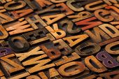 alphabet abstract - vintage wooden letterpress types, stained by color inks, selective focus