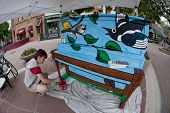 FORT COLLINS, CO. - JUNE 19: A fish eye perspective of artist Ren Burke paints mural on the piano at