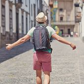 European Man In A Sun Hat Is Travelling Along The Narrow Street Of A European Town. His Arms Are Ope poster