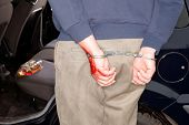 Handcuffed man arrested for drunken driving (bottle in his car)