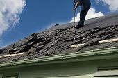 stock photo of shingle  - Removing old shingles to prepare a roof for a new installation with blue sky - JPG