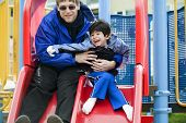 Father Going Down Slide With Disabled Son Who Has Cerebral Palsy