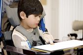 stock photo of disable  - Five year old disabled boy studying in wheelchair - JPG
