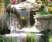 Beautiful cascading waterfall fountain surrounded by plants and flowers