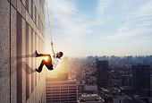 Businessman Climbs A Building With A Rope. Concept Of Determination poster