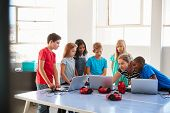 Group Of Students In After School Computer Coding Class Learning To Program Robot Vehicle poster