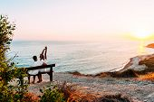 Happy Couple At Sunset. Man And Woman At Dawn. Couple Sitting On A Bench By The Sea. Couple In Love  poster