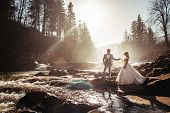 Amazing Wedding Couple, Bride And Groom Holding Hands On A Mountains And Rivers Background. Cute Gir poster