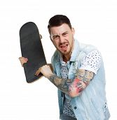 An angry tattooed man attacks. The guy swung to hit the skateboard. Isolated on white background. A  poster