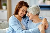 family, generation and people concept - happy smiling senior mother with adult daughter hugging at h poster