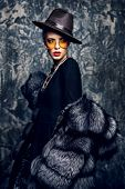 Portrait of a beautiful woman in luxurious fur coat posing in studio. Luxury, rich lifestyle. Fashio poster