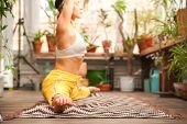 Girl Practicing Yoga On The Veranda With Flowers Close Up And Copy Space. Woman In Yoga Asanas In A  poster