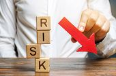 Wooden Blocks With The Word Risk And A Down Arrow. Reduce Financial Risk For Investment And Capital. poster