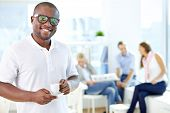 Portrait of happy African guy with cup looking at camera in working environment