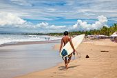 BALI, INDONESIA - JANUARY 13: Unidentified young man with surf board on January 13, 2012. Dreamland