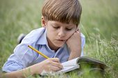 stock photo of pre-adolescent child  - Young people and education school child doing homework laying down on grass at park and studying with book - JPG