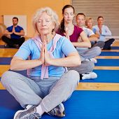Senior woman doing relaxation exercise in yoga class in a gym