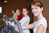 Happy group exercising on crosstrainer in fitness center