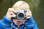Young photographer, holding a retro rangefinder camera in front of his face, taking a picture