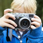Young child, taking a picture using a retro rangefinder camera