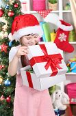 A little girl opens a gift in festively decorated room