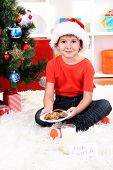 Little boy in Santa hat with milk and cookies for Santa Claus