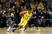 BROOKLYN-DEC 15: Michigan Wolverines guard Trey Burke (3) dribbles past West Virginia Mountaineers D