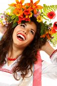Beautiful ukrainian young woman in garland of summer flowers and native costume dancing on Slavic ho