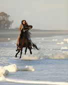woman in formal dress riding wild horse on beach