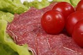 Tomatoes Are On Thin Slices Of Salami And Lettuce