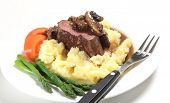 Chateaubriand beef tenderloin steak topped with a mushroom gravy sauce served on a bed of potato wit