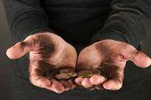 homeless man holding a coins, close-up