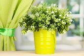 Decorative flowers in pot on windowsill