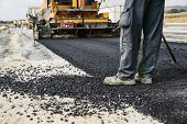 stock photo of machine  - Worker operating asphalt paver machine during road construction and repairing works - JPG