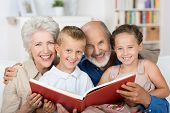 Elderly Couple Reading To Their Grandchildren
