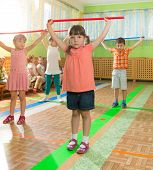 foto of daycare  - Cute little children playing at daycare gym - JPG