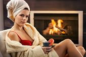 Pretty woman relaxing in bra and bathrobe, enjoying hot tea in front of fireplace.