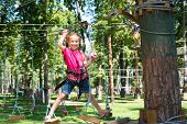 happy little girl  in a rope park on the wood background