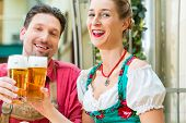 stock photo of chokers  - Young couple in traditional Bavarian Tracht in restaurant or pub with beer - JPG