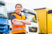 Logistics - proud driver or forwarder in front of trucks and trailers, on a transshipment point