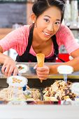 Young Asian saleswoman in an ice cream parlor takes a scoop of ice cream