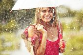 stock photo of mud  - Portrait of beautiful young girl walking with umbrella under rain - JPG