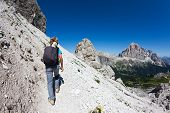 foto of italian alps  - Young hiker walking on a mountain trail - JPG