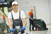 stock photo of cleaning house  - Cleaner male man workers with mop in uniform cleaning corridor pass or hall floor of business building - JPG