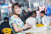 young Chinese waitress girl of street restaurant in china with menu waiting an order