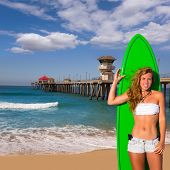 Blond surfer teen girl holding surfboard in Huntington Beach pier California [ photo-illustration]