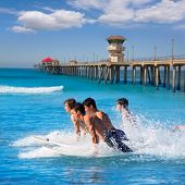 Teenager surfers surfing running jumping on surfboards at Huntington beach pier California [ photo-i